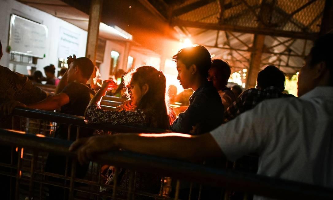 """Pessoas esperam em uma fila para comprar bilhetes de trem em um escritório de emissão de bilhetes em Yangon, antes do festival budista de Ano Novo, conhecido localmente como """"Thingyan"""" Foto: YE AUNG THU / AFP"""