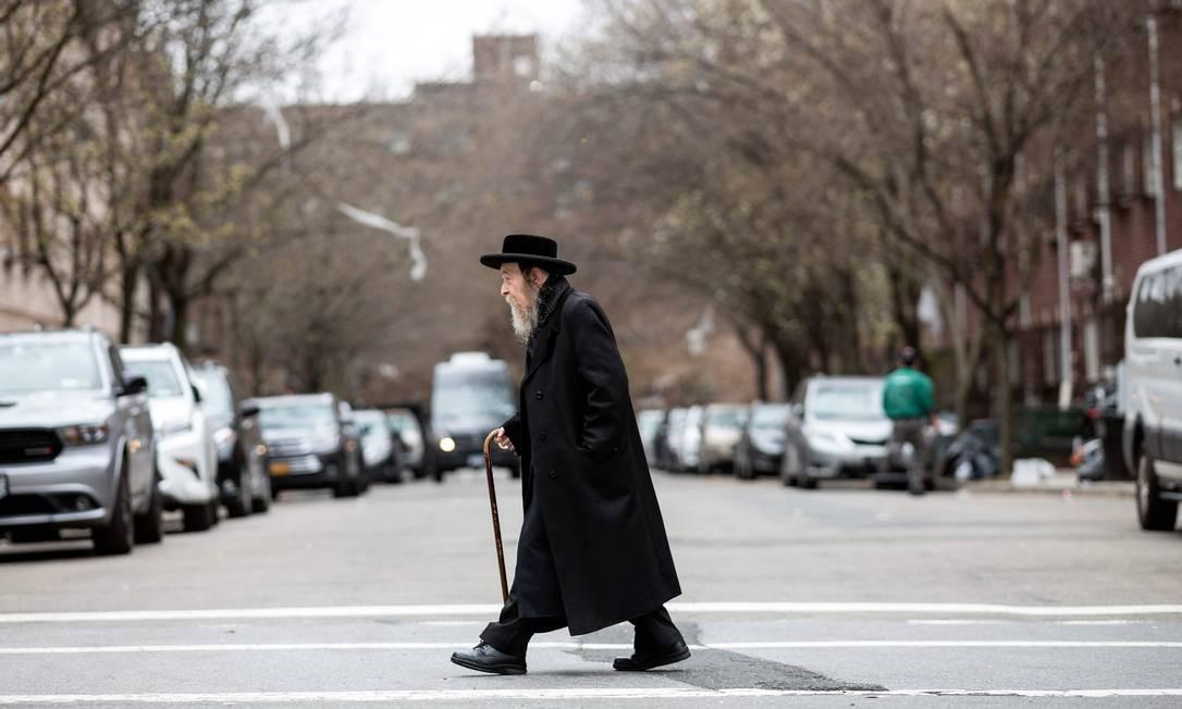 Homem judeu atravessa uma rua em um bairro judeu em Williamsburg, Brooklyn, em Nova York. O prefeito da cidade, Bill de Blasio, declarou uma emergência de saúde pública em parte do Brooklyn, ordenando que todos os residentes recebam a vacina contra o sarampo, em uma tentativa de conter um surto da doença Foto: JOHANNES EISELE / AFP