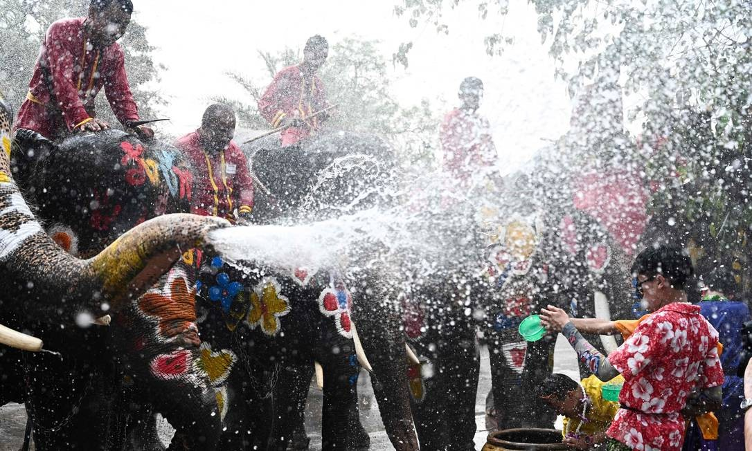 Foliões e elefantes jogam água uns nos outros durante uma cerimônia para celebrar o Ano-Novo Budista, conhecido localmente como Songkran, em Ayutthaya Foto: JEWEL SAMAD / AFP