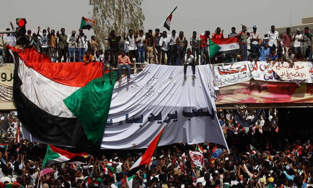 Manifestantes sudaneses se reúnem em uma rua no centro de Cartum após a deposição do presidente do Sudão, Omar Hassan al-Bashir, que estava havia 30 anos no poder. Bashir foi derrubado pelo Exército do país. Os manifestantes rejeitaram a proposta de um governo militar e prometem manter o movimento nas ruas por uma transição civil para um novo governo Foto: ASHRAF SHAZLY / AFP