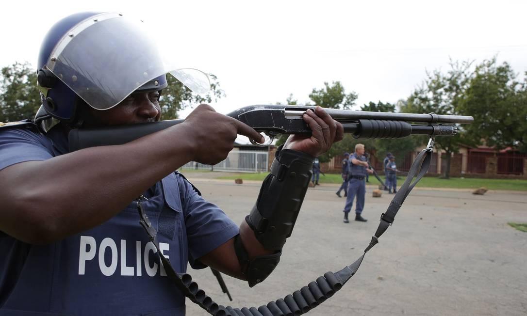Agente dos Serviços de Polícia da África do Sul mira uma arma com o objetivo de dispersar os membros da comunidade de assentamentos informais de Gomora, durante uma manifestação contra a falta de prestação de serviços essenciais, como acesso a água e eletricidade, dificuldades de moradia e falta de vias públicas, em Pretória Foto: PHILL MAGAKOE / AFP