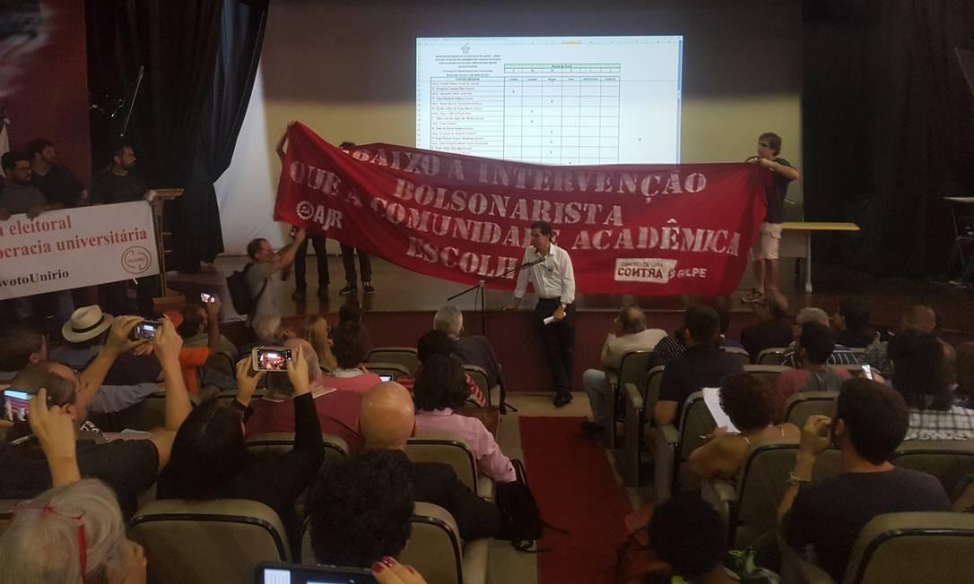 Alunos erguem faixa de protesto durante votação do colégio eleitoral da UniRio Foto: Paula Ferreira