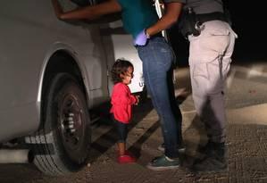 A comovente imagem ganhadora do prêmio World Press Photo de 2019 mostra a menina hondurenha de dois anos chorando enquanto a mãe é revistada na fronteira com os EUA Foto: JOHN MOORE/ GETTY IMAGES NORTH AMERICA/12-06-2018