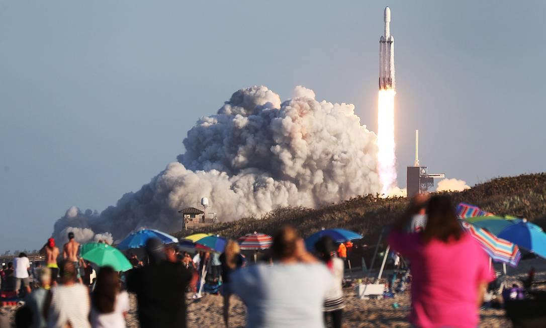 Pessoas observam a decolagem do Falcon Heavy, da SpaceX. Foto: JOE RAEDLE / AFP