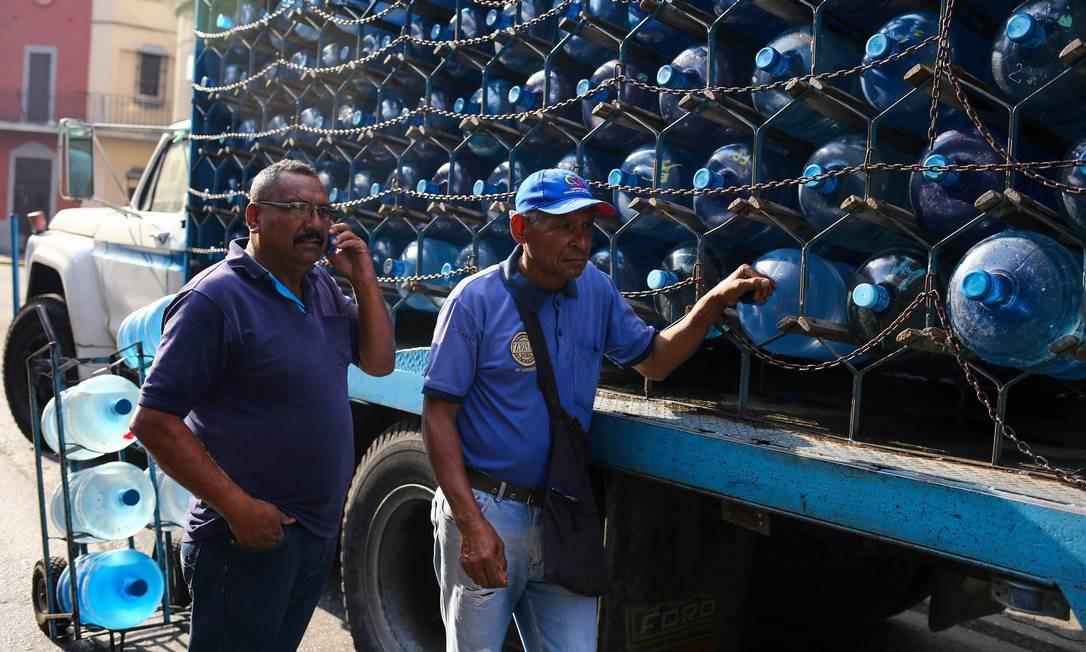Carregamentos de água para população durante corte de energia em Caracas; apagões têm forçado redução das jornadas de trabalho e fechamentos temporários das escolas Foto: CRISTIAN HERNANDEZ / AFP