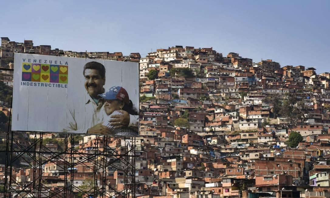 Placa mostra o presidente Nicolás Maduro abraçado à sua mulher, Cilia Flores, com os dizeres 'Venezuela Indestrutível', e, ao fundo, se vê uma das favelas de Caracas; pobres são os mais afetados pela crise humanitária Foto: YURI CORTEZ / AFP