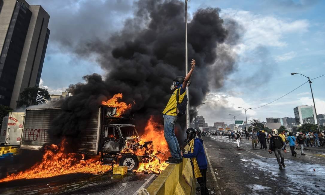 Manifestantes bloqueiam avenida em Caracas e queimam caminhão durante protestos contra o governo em 2017; ondas massivas de marchas são frequentes na Venezuela Foto: JUAN BARRETO / AFP