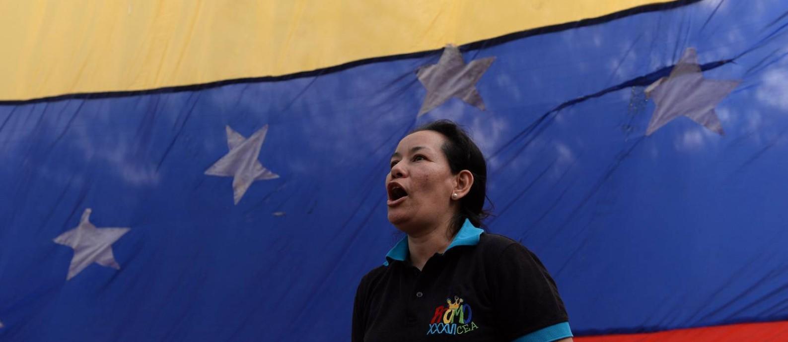 Mulher em frente à bandeira da Venezuela durante manifestação em Caracas; clima político é tenso no país sul-americano Foto: FEDERICO PARRA / AFP