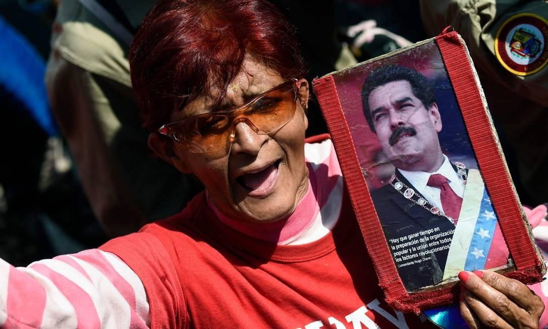 Mulher segura retrato de Nicolás Maduro para mostrar seu apoio ao presidente em Caracas Foto: FEDERICO PARRA / AFP