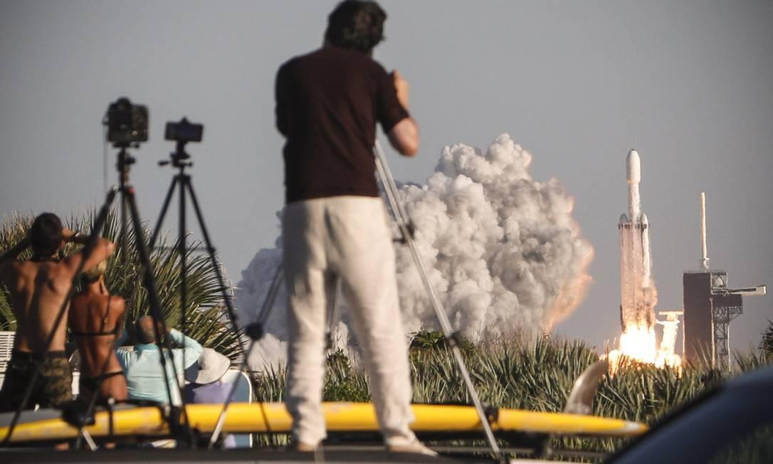 Pessoas observam o lançamento de um foguete SpaceX Falcon Heavy, na Flórida. O Falcon Heavy, da SpaceX, lançou ao espaço seu primeiro voo comercial com a missão de colocar em órbita satélite Arabsat-6A, de empresa saudita Foto: GREGG NEWTON / AFP