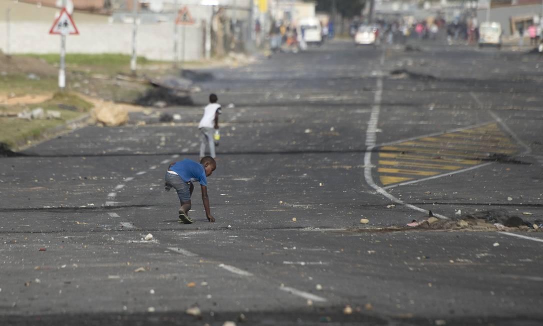 Uma criança pega balas de borracha depois que órgãos da lei expulsaram pessoas que ocuparam ilegalmente um pedaço de terra perto da rodovia N2, uma das principais estradas da África do Sul, perto de Somerset West, a cerca de 60 quilômetros da Cidade do Cabo Foto: RODGER BOSCH / AFP