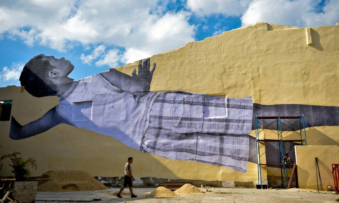Um homem caminha pela obra Gigantes espiando a cidade, uma enorme colagem de uma foto de um menino cubano do artista e fotógrafo francês Jean Réné, também conhecido como JR, como parte da 13ª Bienal de Havana, em Cuba Foto: YAMIL LAGE / AFP
