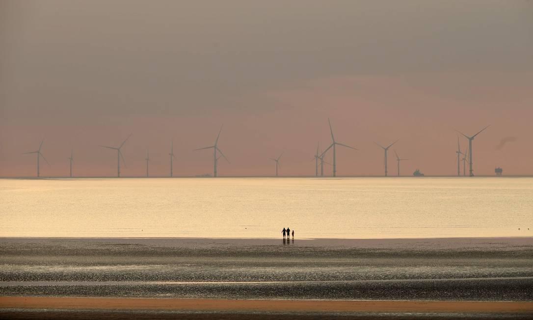 Pessoas caminham na praia em New Brighton, Inglaterra, no pôr do sol, tendo ao fundo Parque Eólico Marítimo do Burbo Bank, no Mar da Irlanda Foto: PAUL ELLIS / AFP