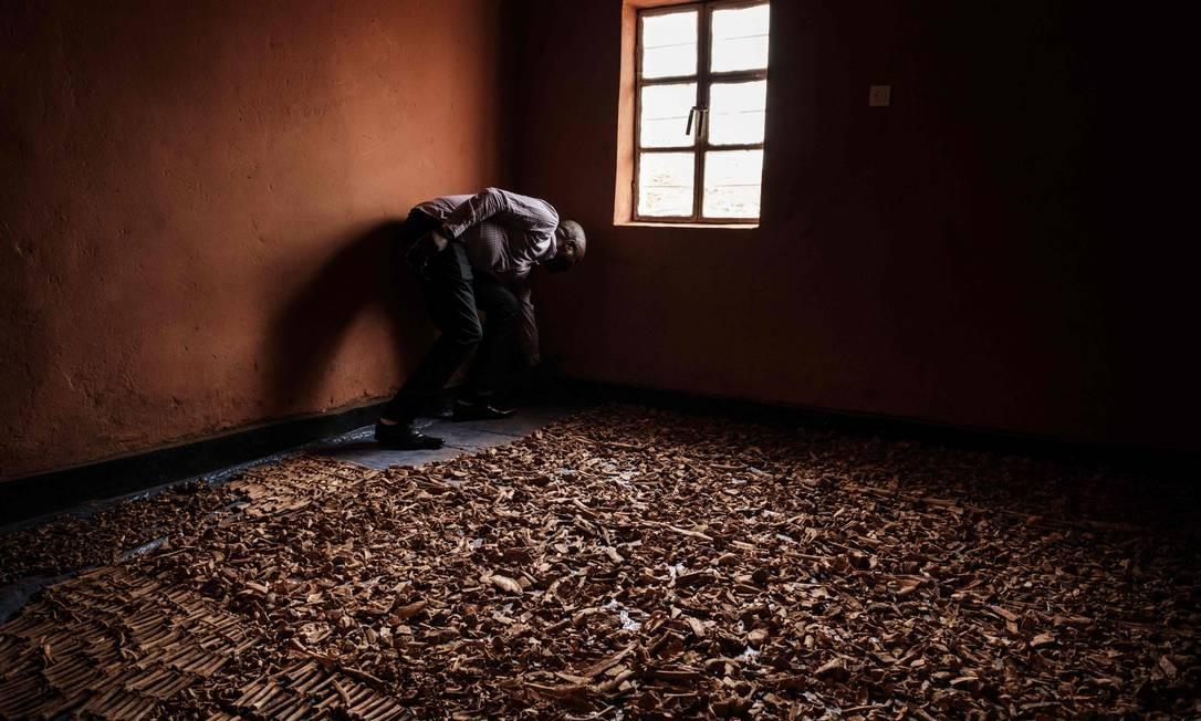 Um homem trabalha perto de ossos das vítimas recuperados de covas que foram usadas como túmulo coletivo durante o genocídio de Ruanda, em 1994, e escondidos sob casas em Kabuga, nos arredores de Kigali. No último dia 7 de abril, Ruanda iniciou 100 dias de luto pelas mais de 800 mil pessoas abatidas em um genocídio que chocou o mundo, 25 anos depois Foto: YASUYOSHI CHIBA / AFP