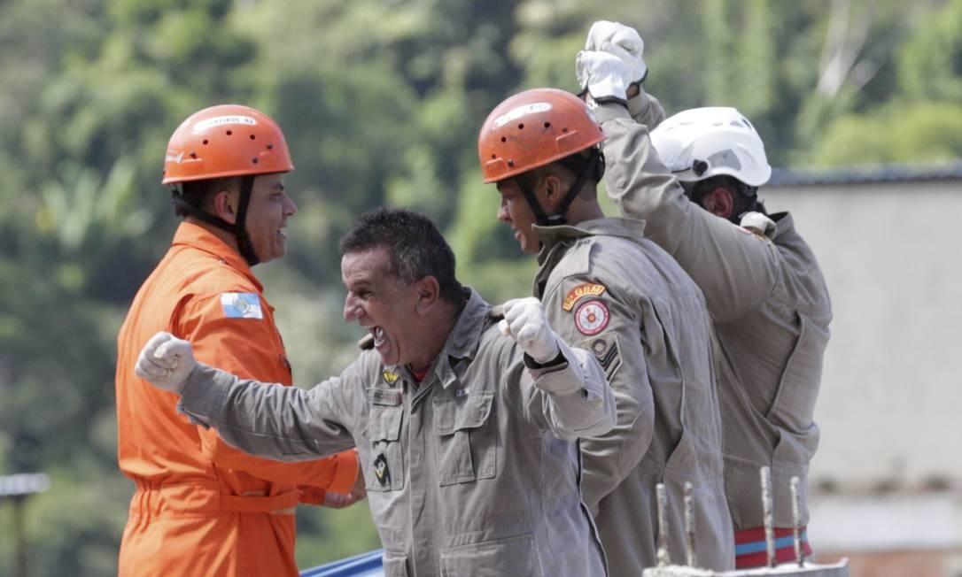 Bombeiros comemoram após resgatarem uma vítima com vida e colocá-la no helicóptero Foto: Márcio Alves / Agência O Globo