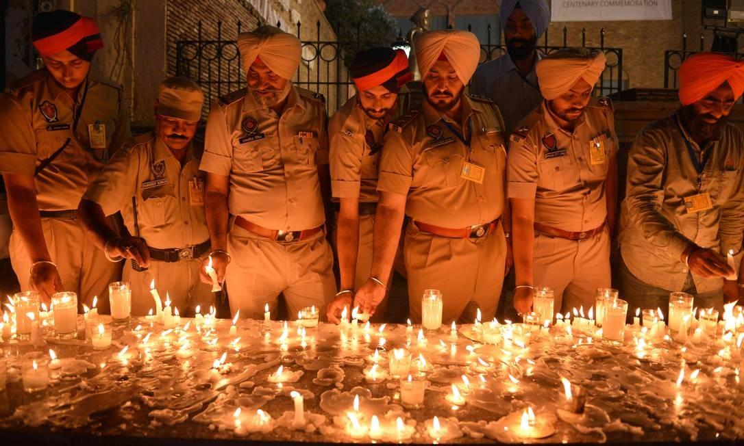 Policiais indianos do Punjab acendem velas em homenagem aos massacres de Jallianwala Bagh, na véspera do centésimo aniversário do evento sangrento, em Amritsar. O massacre de Amritsar ocorreu em 13 de abril de 1919, quando soldados do exército indiano britânico, sob ordens diretas de seus oficiais britânicos, abriram fogo contra uma reunião desarmada, matando pelo menos 379 homens, mulheres e crianças, segundo registros oficiais Foto: NARINDER NANU / AFP