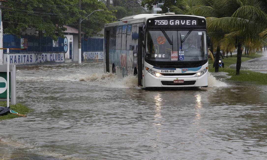Ônibus atravessa a Avenida Silvio Picanço: moradores dizem que água demorou mais de um dia para escoar Foto: Fábio Guimarães / Agência O Globo