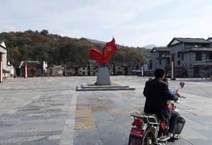 Homem e criança passam de moto por praça com o emblema do Partido Comunista na vila de Shazhou, província de Hunan: China quer melhorar economia do interior para conter crescimento das grandes cidades Foto: Shu Zhang/REUTERS/03-12-2018
