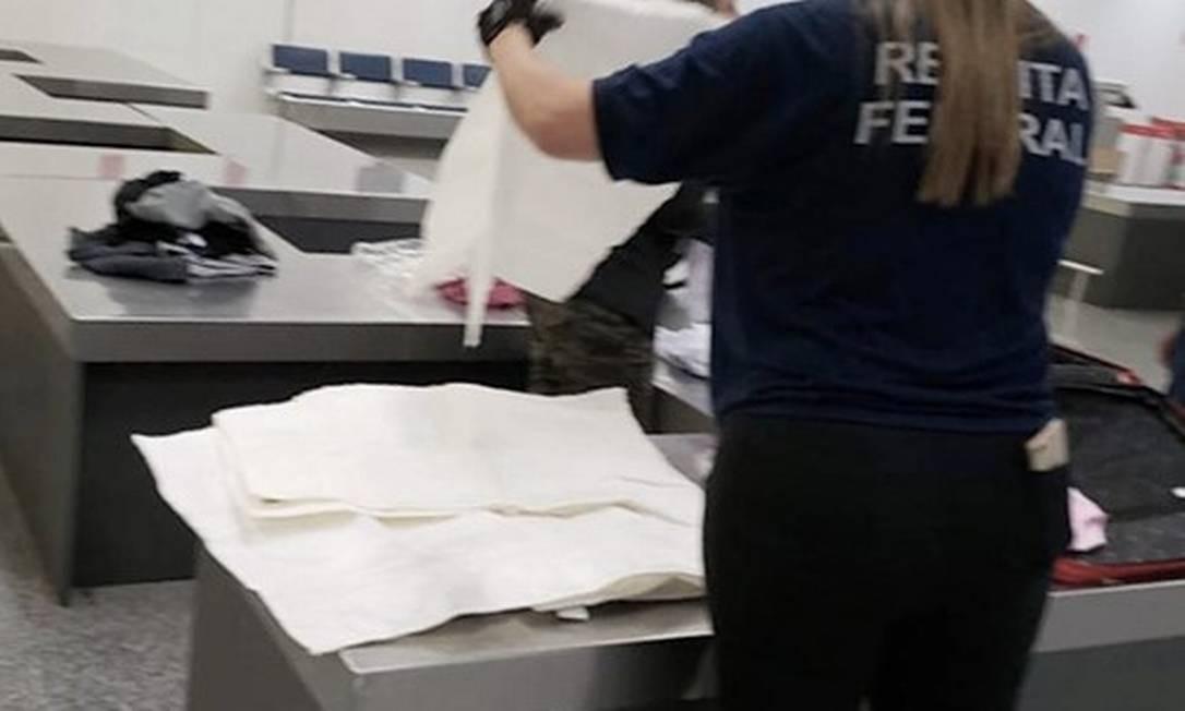 Uma fiscal da Receita Federal manuseia as peças engomadas com a cocaína Foto: Receita Federal / Divulgação