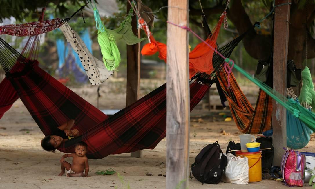 Uma indígena Macuxi deitada em uma rede enquanto uma criança se senta no chão na comunidade de Maturuca, na reserva Raposa Serra do Sol, estado de Roraima Foto: BRUNO KELLY / REUTERS