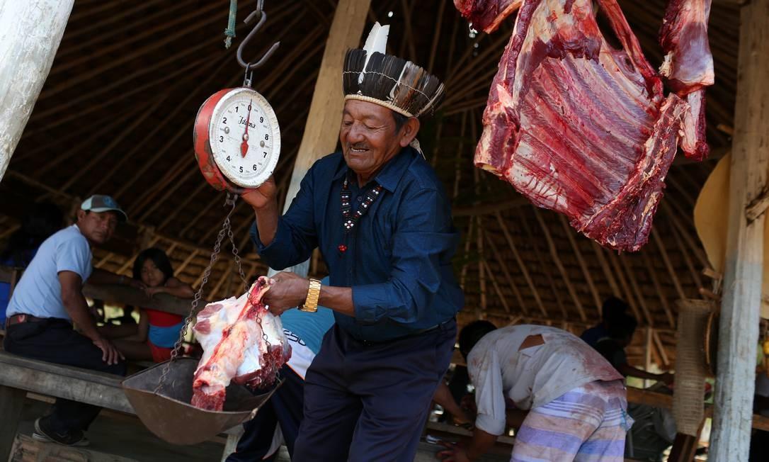 Líder Macuxi Orlando Pereirana da Silva, 73 anis, pesa pedaços de carne na comunidade Uailan, na reserva Raposa Serra do Sol reservation Foto: BRUNO KELLY / REUTERS
