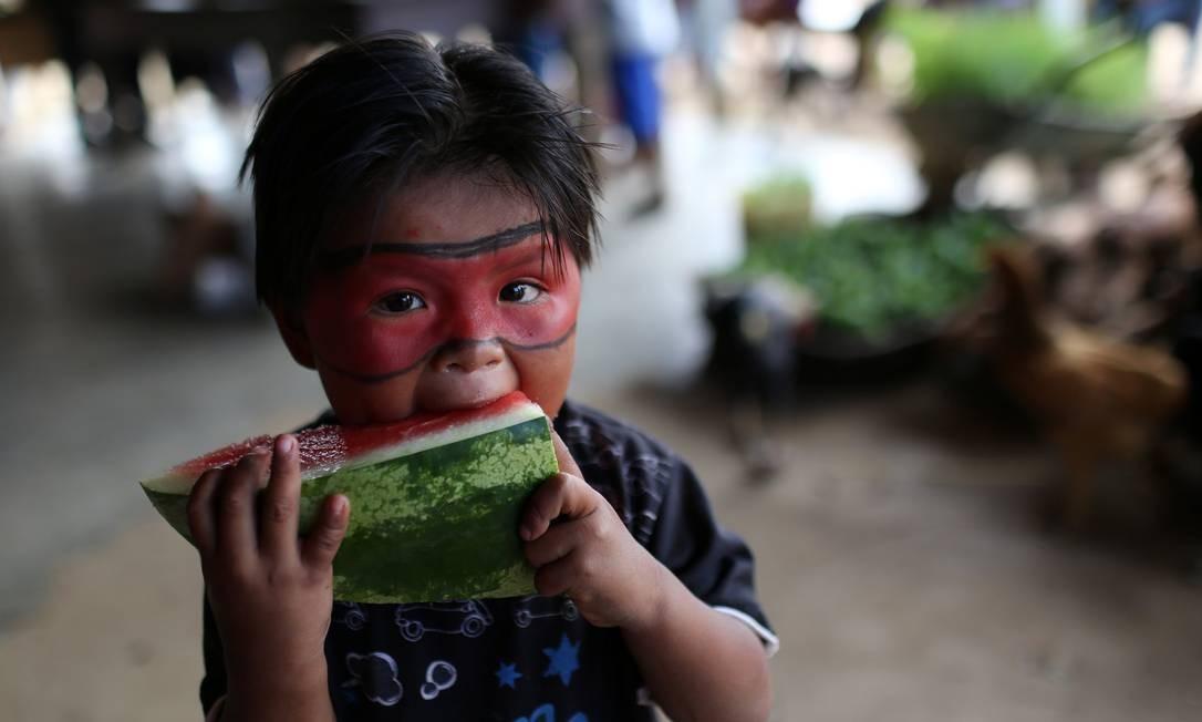 Uma criança Macuxi come melancia na comunidade de Uailan, na reserva Raposa Serra do Sol Foto: BRUNO KELLY / REUTERS