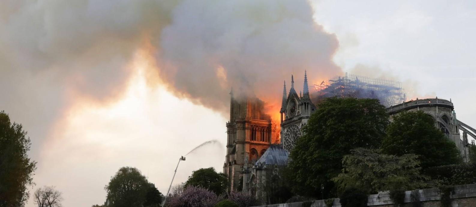 Chamas e fumaça emanam da catedral de Notre Dame em Paris Foto: THOMAS SAMSON / AFP