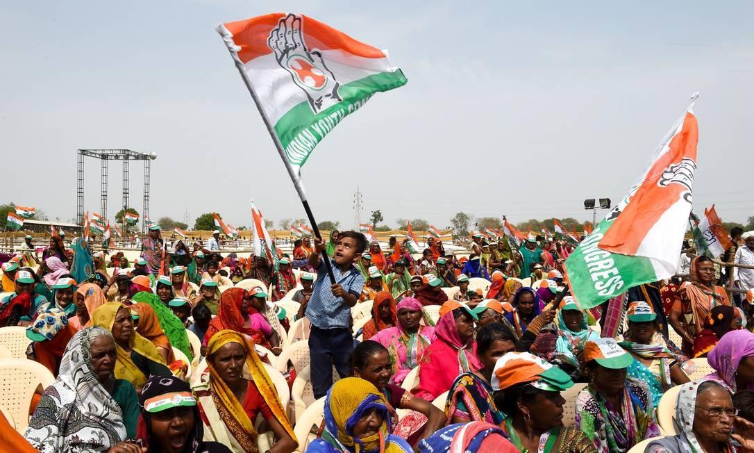 Um jovem indiano tremula uma bandeira do partido do Congresso Nacional durante um comício do presidente Rahul Gandhi, na vila de Asarana, em Bhavnagar, a cerca de 300 quilômetros de distância da cidade de Ahmedabad Foto: SAM PANTHAKY / AFP