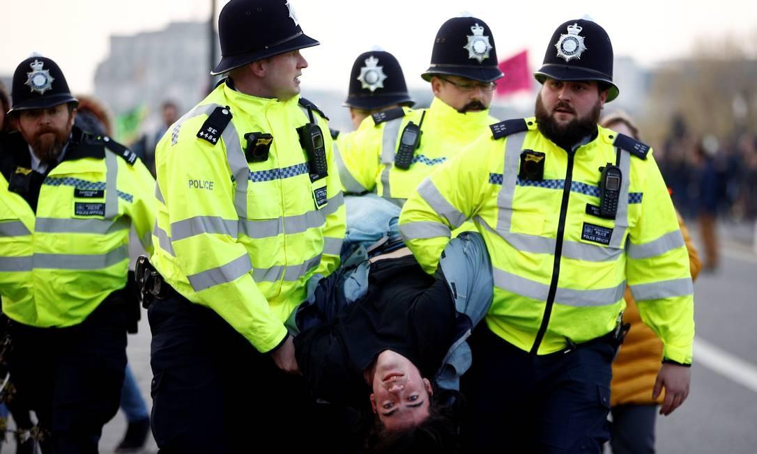 """Polícia inglesa detém um ativista do clima durante um protesto na ponte Waterloo, em Londres. Manifestantes participam do protesto chamado de """"Extinction Rebellion"""" — Rebelião da Extinção, em inglês. Foto: HENRY NICHOLLS / REUTERS"""