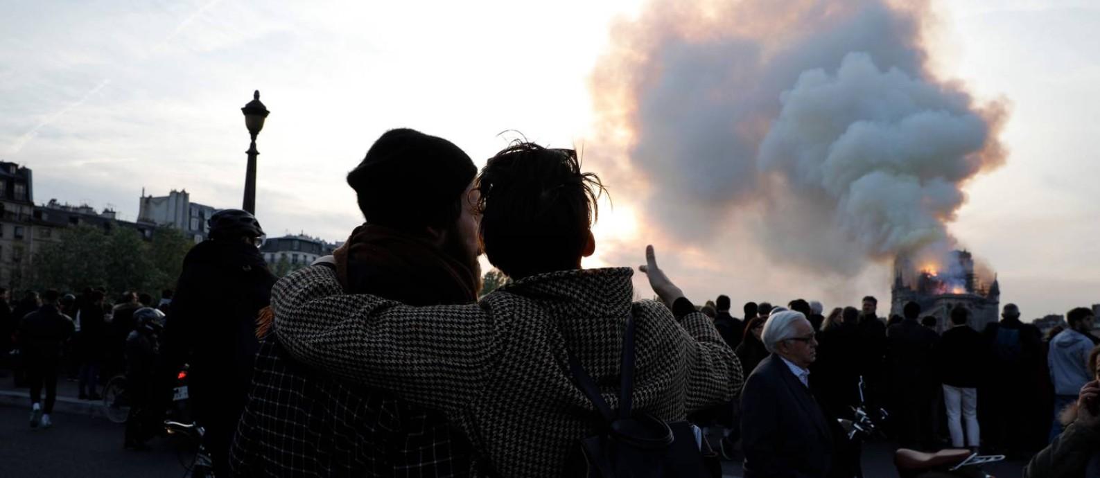 Pessoas observam o incêndio na Catedral de Notre Dame, em Paris: multidão permaneceu em silêncio Foto: GEOFFROY VAN DER HASSELT / AFP