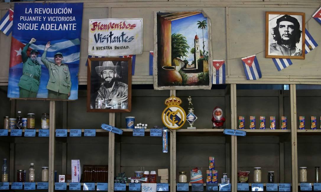 Posteres mostrando o falecido líder cubano Fidel Castro, seu irmão Raúl, ex-presidente e agora chefe do Partido Comunista, e o revolucionário Che Guevara junto aos dizeres 'a pujante e vitoriosa revolução segue adiante' em uma 'bodega', tipo de loja onde os cubanos compram produtos básicos com cartões de racionamento distribuídos anualmente pelo governo: medo de desabastecimento com renovada pressão econômica dos EUA contra o país e a aliada Venezuela Foto: FERNANDO MEDINA/REUTERS/10-04-2019