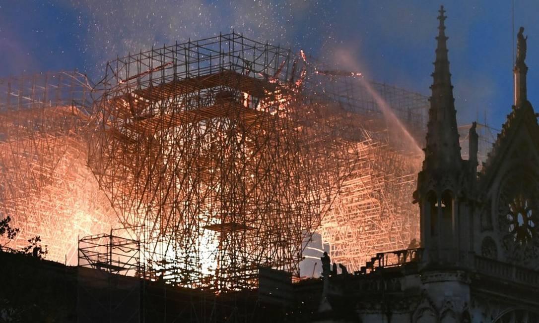 As chamas atingem o telhado, onde andaimes eram usados nas obras da Catedral de Notre Dame de Paris Foto: STEPHANE DE SAKUTIN / AFP