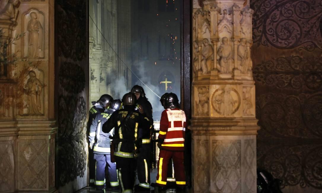 Bombeiros tentam entrar na nave da catedral em Paris, que recebe a visita de 13 milhões de pessoas por ano Foto: PHILIPPE WOJAZER / REUTERS