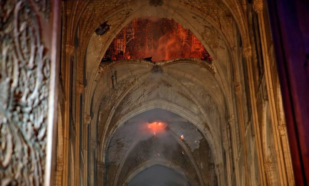 Fumaça e chamas são observadas no interior da Notre-Dame, cuja construção começou no século XII Foto: PHILIPPE WOJAZER / REUTERS