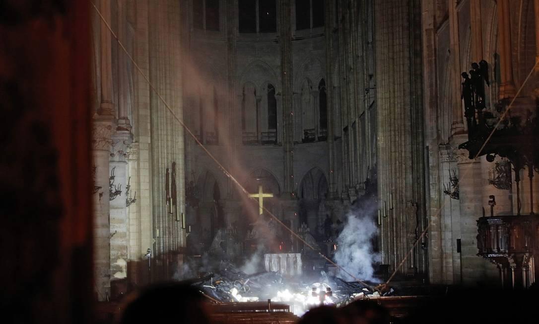 Fumaça sobe do altar da Catedral de Notre-Dame. A torre pontiaguda ruiu, mas as duas dos sinos se salvaram Foto: PHILIPPE WOJAZER / AFP
