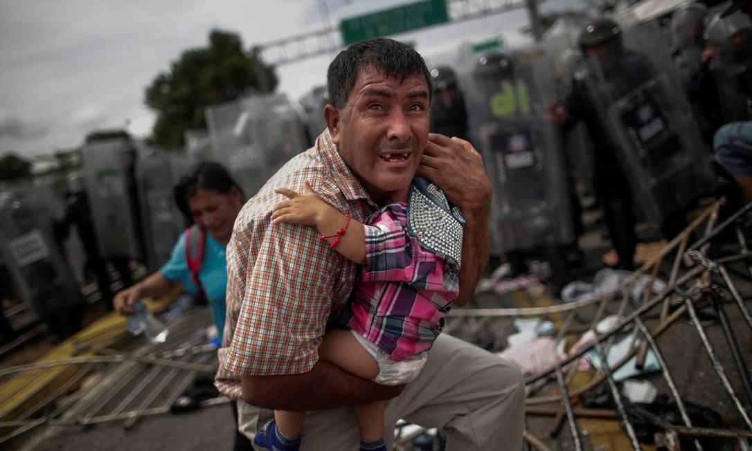 Imigrante hondurenho protege filha durante caravana até a fronteira sul dos Estados Unidos Foto: UESLEI MARCELINO / REUTERS
