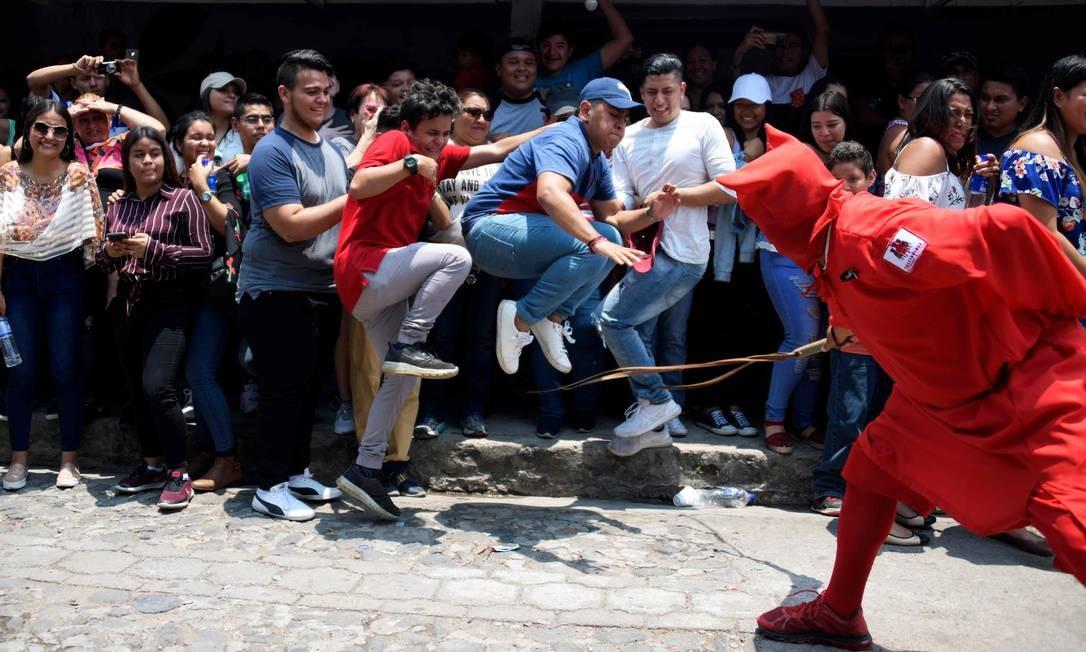 Um homem vestido com uma fantasia que repesenta um demônio distribui chicotadas para ilustrar a eterna luta do bem contra o mal. Os talciguines, como são conhecidos no idioma local, açoitam os espectadores para puni-los por seus pecados durante cerimônia que marca o início da Semana Santa em Texistepeque, cerca de 80 km a oeste de El Salvador Foto: MARVIN RECINOS / AFP