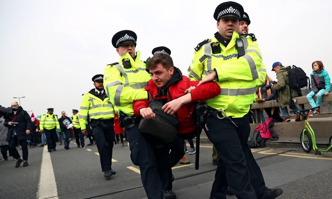 Policiais detêm um ativista da mudança climática na Ponte de Waterloo, durante o protesto da Rebelião da Extinção em Londres Foto: HANNAH MCKAY / REUTERS
