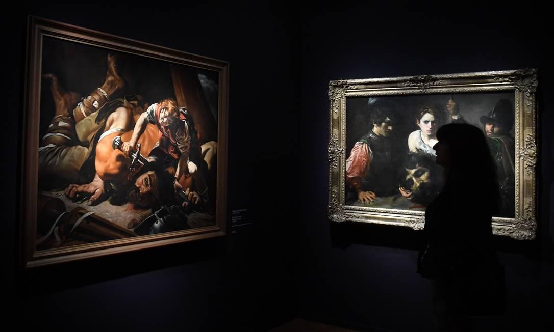 """Uma mulher observa as pinturas """"David com cabeça de Golias e dois soldados"""", por Valentin de Boulogne, e """"David e Golias"""", por Orazio Borgianni, durante uma pré-visualização da exposição de arte """"Utrecht, Caravaggio e Europa"""", no museu Alte Pinakothek, em Munique, Alemanha. A exposição será aberta ao público nesta quarta-feira (17) Foto: CHRISTOF STACHE / AFP"""