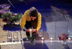 Mulher acende vela em Paris em local onde franceses lamentam o incêndio da Catedral de Notre-Dame Foto: GONZALO FUENTES / REUTERS