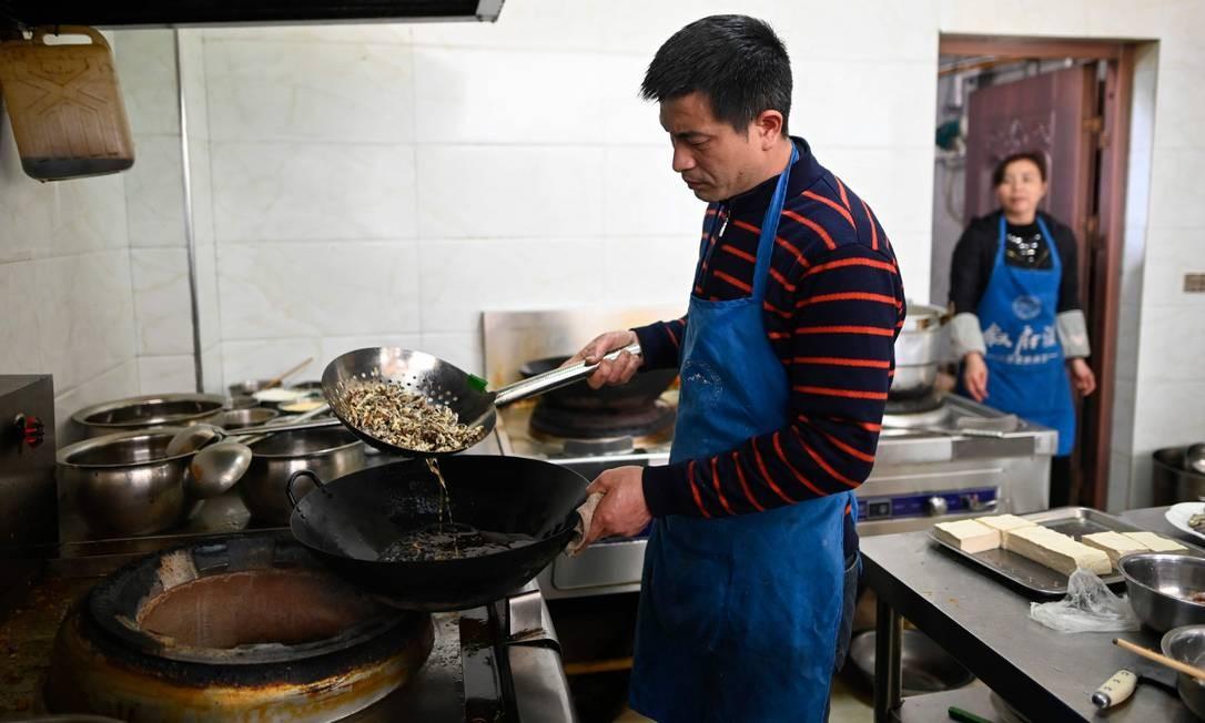Um cozinheiro frita baratas em um restaurante em Yibin, sudoeste da província de Sichuan Foto: WANG ZHAO / AFP