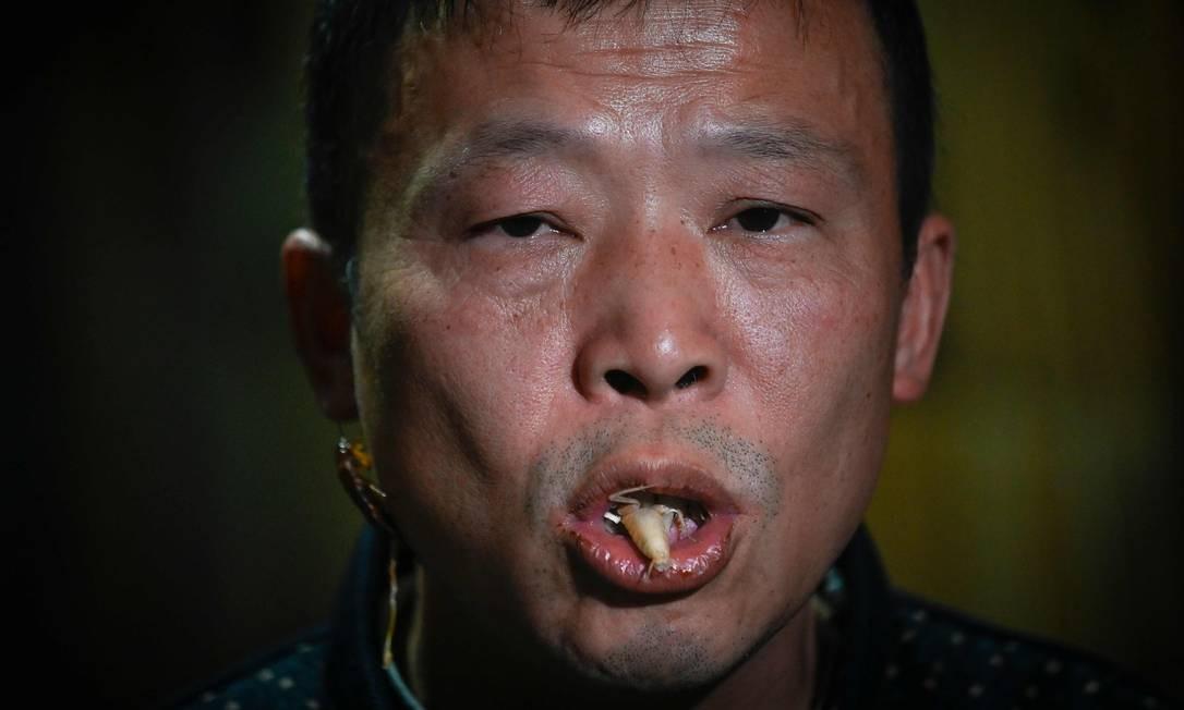 Li Bingcai mastiga uma barata de sua fazenda Foto: WANG ZHAO / AFP