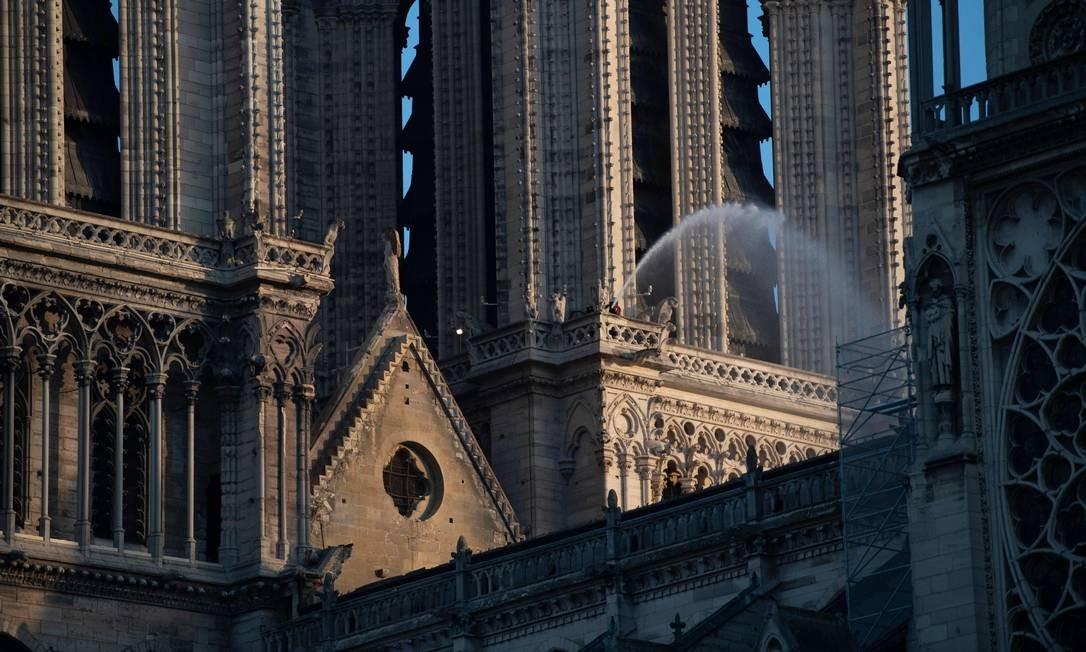 Um bombeiro lança água sobre a torre ao norte da catedral Notre-Dame de Paris, após o incêndio que devastou a principal igreja parisiense Foto: ERIC FEFERBERG / AFP