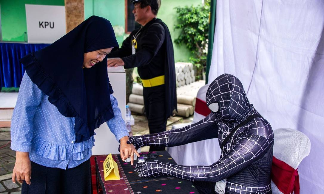 Operários eleitorais indonésios vestidos com trajes de super-heróis registram eleitores em uma seção eleitoral em Surabaya. A Indonésia deu início a uma das maiores eleições de um dia do mundo, colocando o presidente Joko Widodo contra o ex-general Prabowo Subianto em uma corrida para liderar a nação de maioria muçulmana Foto: JUNI KRISWANTO / AFP