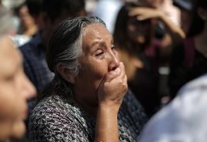 Mulher chora do lado de fora de hospital onde ex-presidente do Peru Alan García se submetia a cirurgia após atirar contra si mesmo Foto: LUKA GONZALES / AFP