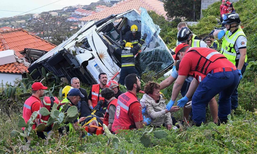 Bombeiros ajudam vítimas de acidente de ônibus em Caniço, na Ilha da Madeira em Portugal. Pelo menos 28 pessoas morreram em decorrência da queda Foto: RUI SILVA / AFP
