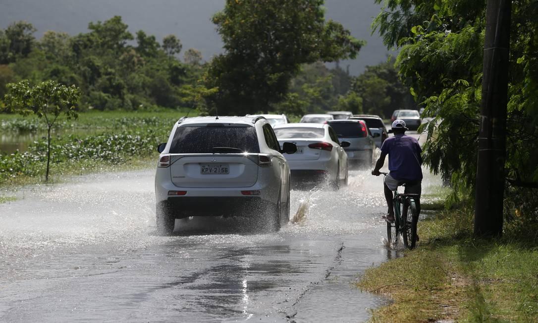 O canal na Estrada do Rio Morto transborda e a água invade a pista quando chove muito Foto: Pedro Teixeira / Agência O Globo