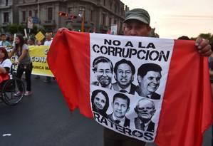Homem carrega bandeira com os rostos de ex-presidentes e de ex-primeira-dama do Peru acusados de corrupção durante protesto em 2017 Foto: CRIS BOURONCLE / AFP/16-02-2017