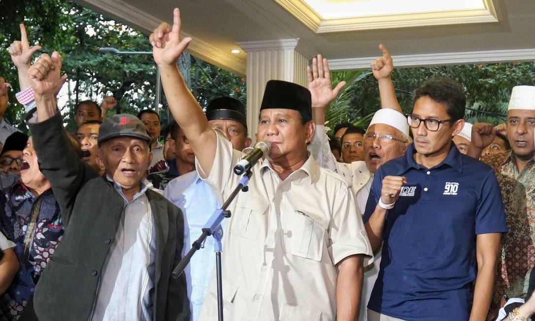Candidato opositor Prabowo Subianto, ao centro, declara vitória em eleições presidenciais da Indonésia; o presidente Joko Widodo fez o mesmo Foto: IZAAK / AFP