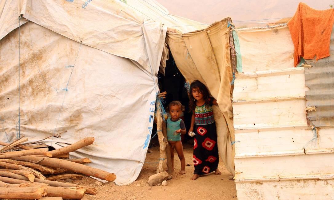 Crianças que fugiram da guerra no Iêmen se abrigam em tendas de campo de deslocados; o país vive uma das maiores crises humanitárias do mundo com elevados índices de pobreza e desnutrição Foto: ESSA AHMED / AFP